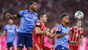 Bayern Munich's Polnish striker Robert Lewandowski (C) and Leverkusen's German defender Benjamin Henrichs (R) vie for the ball during the German First division Bundesliga football match FC Bayern Munich vs Bayer