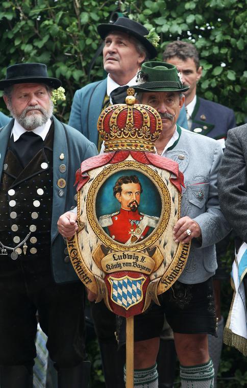 Uczestnicy mszy z okazji obchodów 125. rocznicy śmierci Ludwika II w tradycyjnych strojach bawarskich, z portretem króla