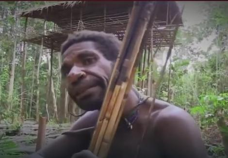 Muškarac ispred kuće na drvetu u pozadini