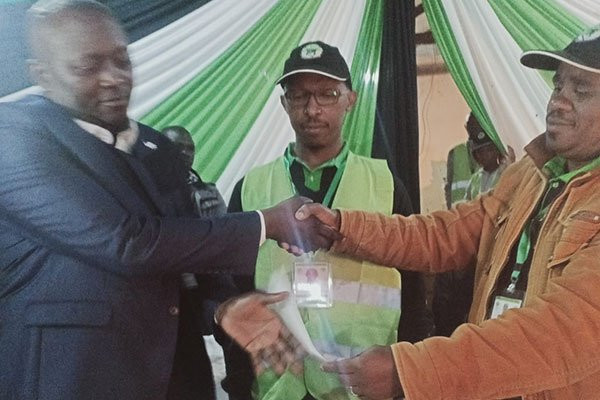 Musee Mati of Maendeleo Chap Chap (left) receives the IEBC election certificate for Mutonguni Ward