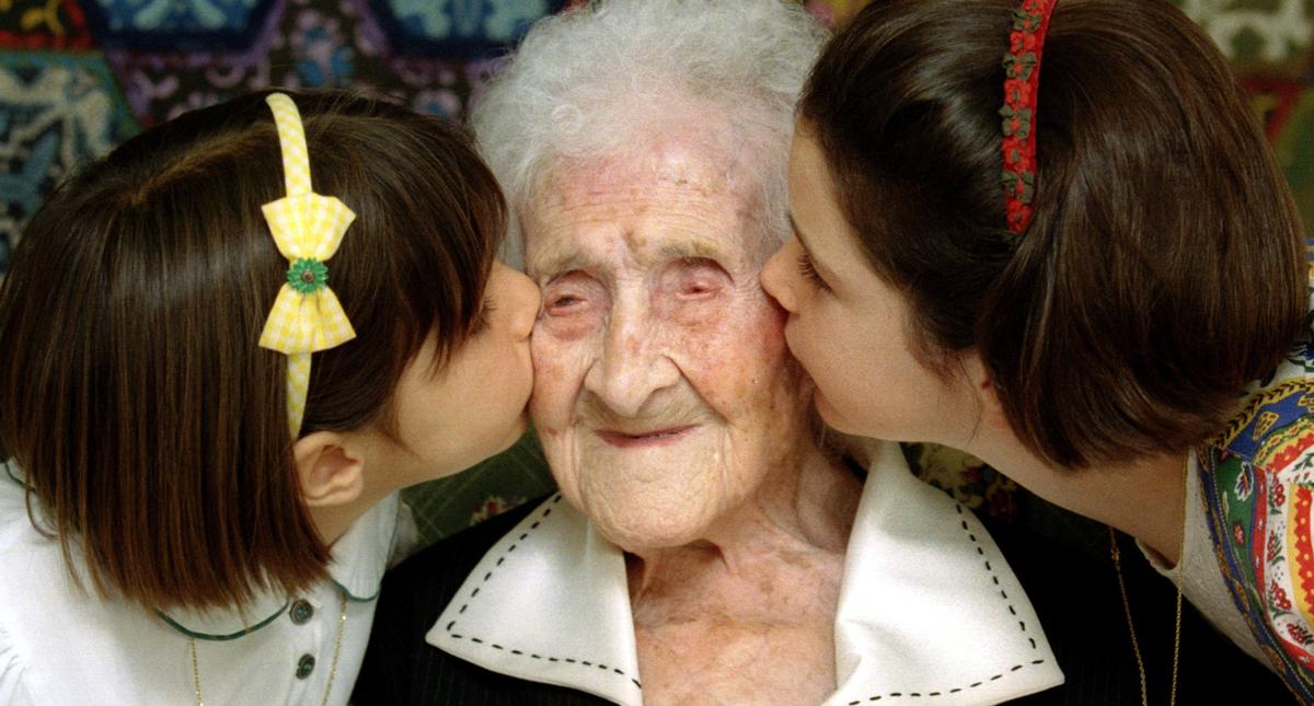 The World's oldest woman, Jeanne Calment, 120 years old, is kissed by two young girls during a speci