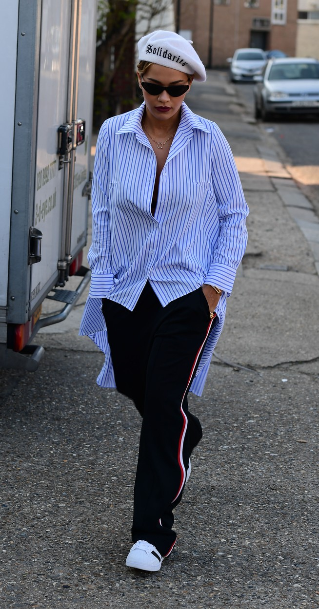 Rita Ora iskombinovala je dva aktuelna trenda, pantalone sa crtom i glomaznu košulju sa sitnim prugama