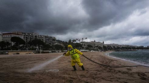 Mężczyzna spryskuje środkiem dezynfekującym plażę na Riwierze Francuskiej w Cannes. Fot. VALERY HACHE / AFP