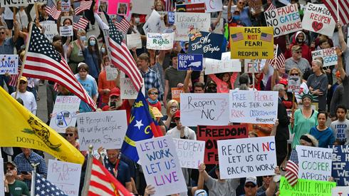 Setki mieszkańców Karoliny Północnej w USA protestowały przy domu gubernatora Roya Coopera przeciw ograniczeniom, jakie zarządził w związku z epidemią koronawirusa, w tym przeciw uderzającemu w gospodarkę nakazowi pozostania w domu (fot. PAP/Abaca)