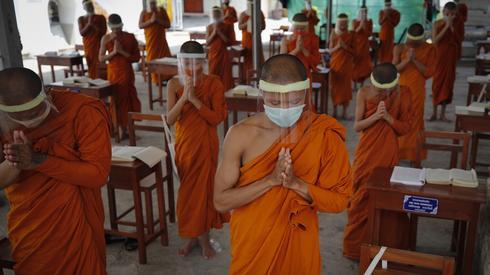 Koronawirus. Buddyjscy mnisi w przyłbicach. Autor: PAP/EPA/Diego Azubel