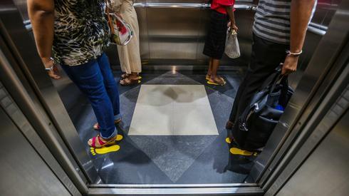 W windzie w Urzędzie ds. Imigracji na Sri Lance naklejono specjalne oznaczenia w jaki sposób należy w niej przebywać (PAP/EPA/CHAMILA KARUNARATHNE)