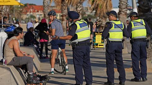 Funkcjonariusze służb ochronnych Victoria Police rozmawiają z mężczyzną na plaży St Kilda w Melbourne. Zamknięto nieistotne usługi w całej Australii w celu spowolnienia rozprzestrzeniania się choroby COVID-19. Fot. PAP/EPA/Scott Barbour