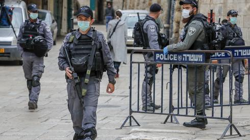Jerozolima. Izraelscy członkowie siły bezpieczeństwa noszący maski ochronne. Fot. AHMAD GHARABLI / AFP