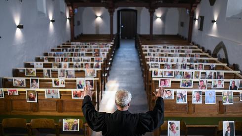 Niemcy. Ewangelicki pastor stoi przed zdjęciami wiernych w ławach kościelnych. Fot. Ina FASSBENDER / AFP