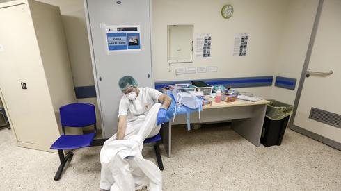 Członek personelu medycznego zakłada strój ochronny, przed rozpoczęciem dnia pracy na oddziale intensywnej terapii w szpitalu w Rzymie. Fot. RICCARDO DE LUCA / ANADOLU AGENCY / AFP