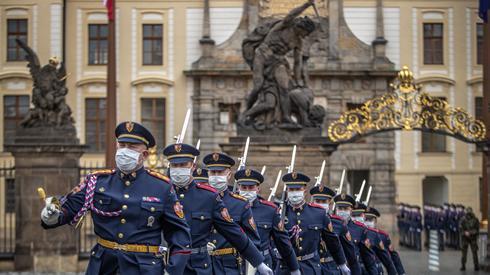 Członkowie Gwardii Zamkowej w Pradze maszerują w maseczkach, podczas zmiany warty / Foto: Martin Divisek / PAP