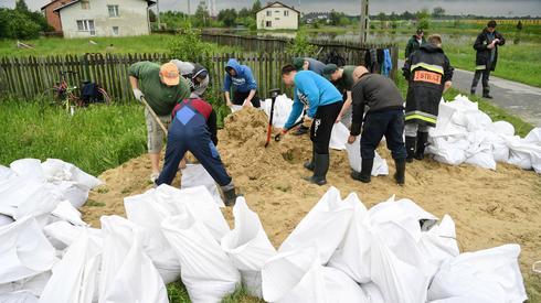 Strażacy i mieszkańcy przygotowują worki z piaskiem w Przyszowie. Na Podkarpaciu pogotowie przeciwpowodziowe obowiązuje w 7 powiatach (fot. PAP/Darek Delmanowicz)