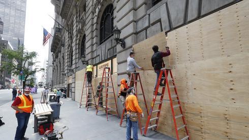 Pracownicy w centrum Nowego Jorku zabezpieczają swoje sklepy przed spodziewanymi demonstracjami / fot. JUSTIN LANE, PAP