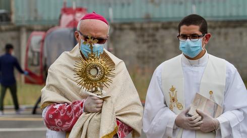 Biskup pomocniczy w Ekwadorze Giovanni Battista Piccioli (L) z maseczką i rękawiczkami. Duchowny przygotowuje się do wejścia na pokład helikoptera, aby z powietrza udzielić błogosławieństwa. Fot. Enrique Ortiz / AFP