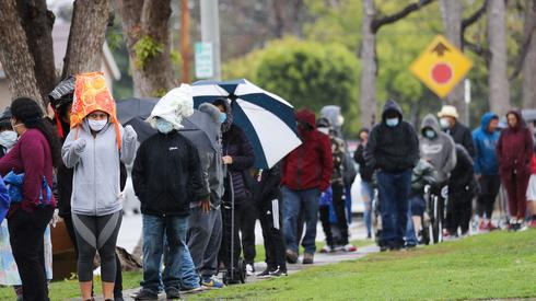 Kalifornia. Ludzie czekają w kolejce po jedzenie z banku żywności dla potrzebujących. Pandemia zrujnowała wiele amerykańskich rodzin.  Fot. MARIO TAMA / GETTY IMAGES NORTH AMERICA/AFP