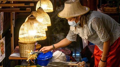 Mladen ANTONOV / AFP, Uliczna sprzedawczyni żywności w Bangkoku nosząca maskę ochronną