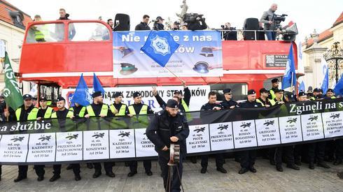 Funkcjonariusze przygotowali na dzisiejszą manifestację transparent przedstawiający nazwiska tych, którzy polegli na służbie. Fot. Radek Pietruszka/PAP