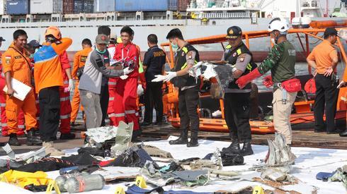 Służby zbierają na brzegu szczątki pochodzące z samolotu/ fot. Bagus Indahono PAP/EPA