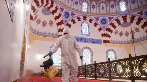 Pracownik rozpyla środek dezynfekujący wewnątrz meczetu Bania Baszi Dżamija w Sofii, Fot. NIKOLAY DOYCHINOV / AFP