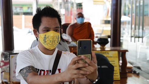 Tajlandzyk z maską ochronną robi zdjęcie z tajskim mnichem buddyjskim w tle podczas Songkran w Bangkoku. Festiwal Songkran odbywa się co roku z okazji tradycyjnego tajlandzkiego Nowego Roku 13 kwietnia. Ludzie oblewają się wodą nawzajem i posypują sobie twarze proszkiem jako symboliczny znak oczyszczenia i zmywania grzechów z ubiegłego roku. Festiwal Songkran został odwołany w całym kraju, aby zapobiec rozprzestrzenianiu się COVID-19. Fot: PAP / EPA? Diego Azubel.