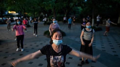 Chinki ćwiczą w parku w Wuhan. Fot. Hector RETAMAL / AFP