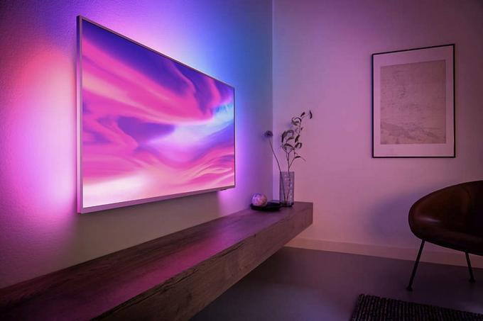 Telewizor z Ambilight powieszony na ścianie