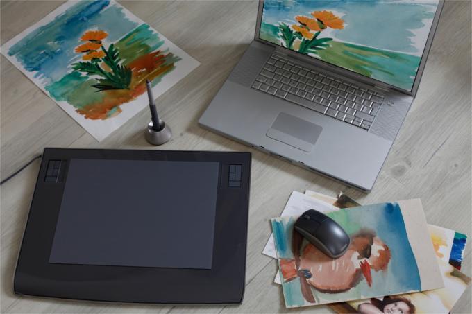 Tablet graficzny obok myszki i laptopa