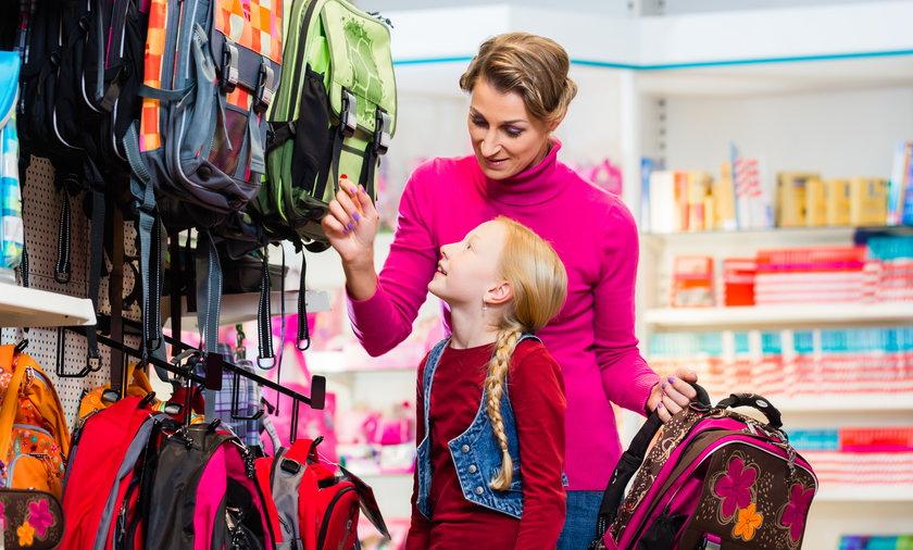 Family buying school satchel or bag in store