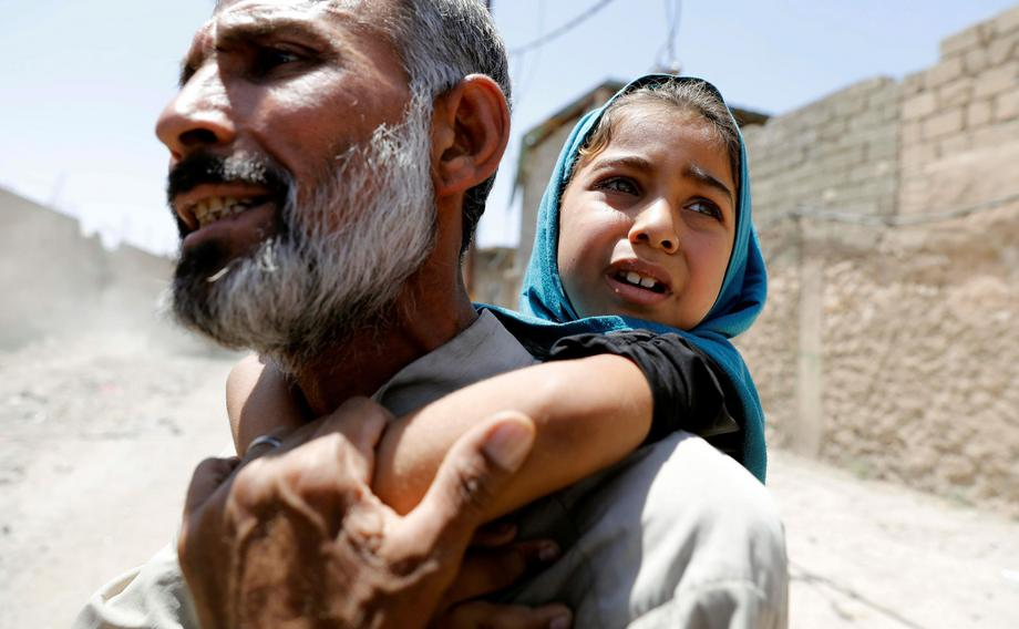 A man carries his daughter on his back after fleeing their home due to fighting between the Iraqi fo