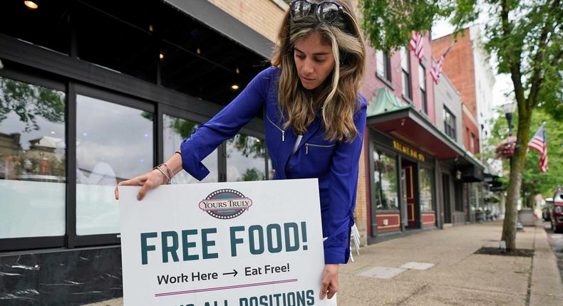 Coleen Piteo, director of marketing at Yours Truly restaurant, puts out a sign for hiring, Thursday, June 3, 2021, in Chagrin Falls, Ohio.