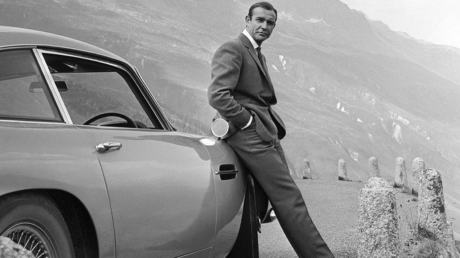 """Sean Connery pozuje jako James Bond obok Astona Martina DB5 podczas sesji przed premierą filmu """"Goldfinger"""""""