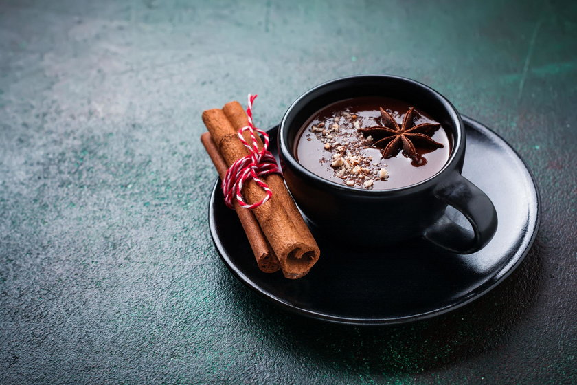 Hot chocolate with anise and nuts in black ceramic cup on old dark green concrete background. Select