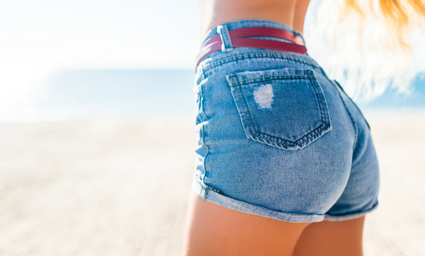 Woman showing her sexy curves. Hips and legs body part in short denim shorts.