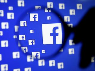 A man poses with a magnifier in front of a Facebook logo on display in this illustration taken in Sa