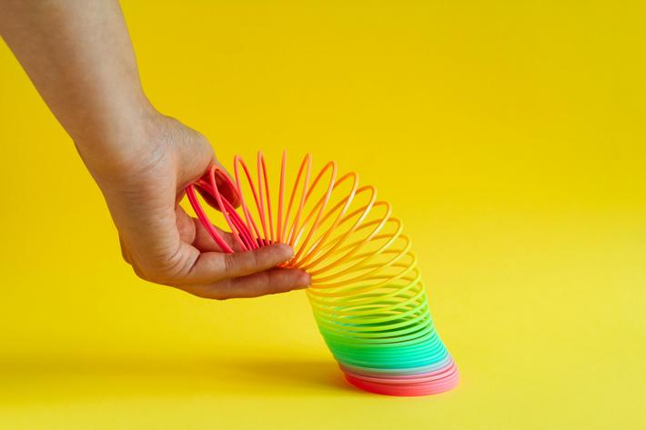 hands stretched plastic rainbow spiral