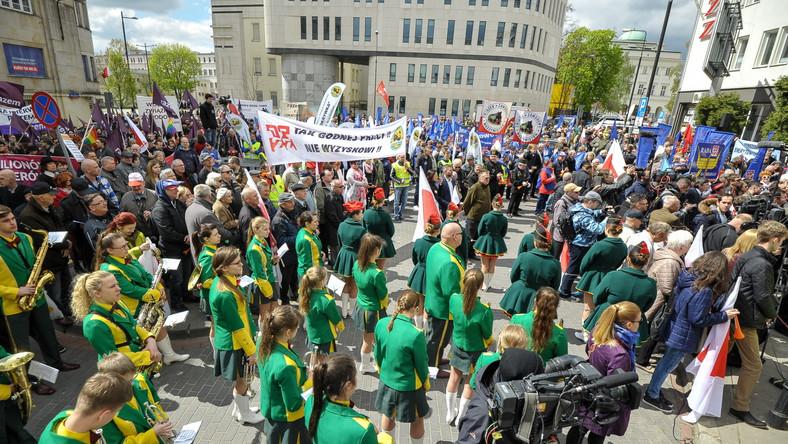 """Na przedzie maszeruje w zielono-żółtych strojach Młodzieżowa Orkiestra Dęta z Ostrowi Mazowieckiej i grupa górników w strojach galowych. Uczestnicy manifestacji trzymają biało-czerwone flagi, na niektórych jest napis """"PPS"""", są flagi biało-czerwone SLD, niebieskie OPZZ i fioletowe partii """"Razem"""". Jej przedstawiciele trzymają transparenty z napisami """"Polska dla milionów - nie dla milionerów"""" i """"Najpierw ludzie, potem zyski"""". Działacze """"Pracowniczej Demokracji"""" niosą tablice - m.in. z napisem """"Kapitalizm oznacza nędzę, rasizm, wojnę i katastrofę klimatyczną. Inny świat jest możliwy"""""""