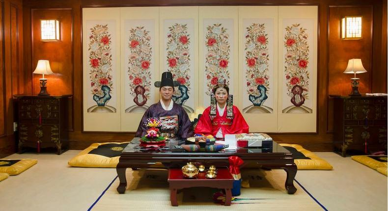 A korean couple pose for pictures at their wedding ceremony