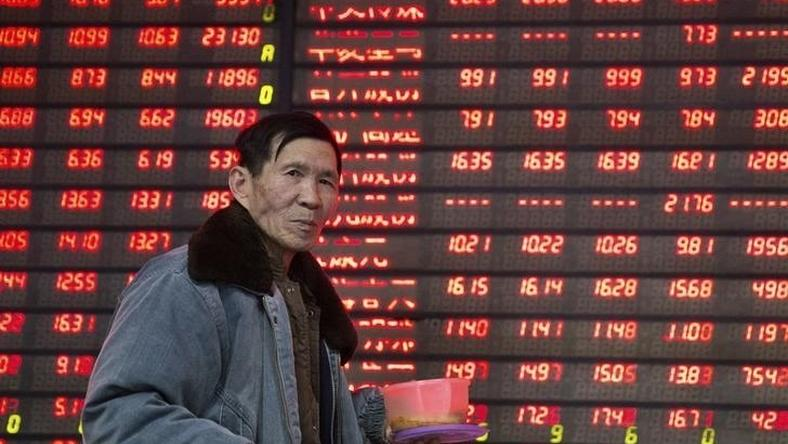 An investor walks past an electronic screen showing stock information at a brokerage house in Nanjing, Jiangsu province, China January 14, 2016. REUTERS/China Daily