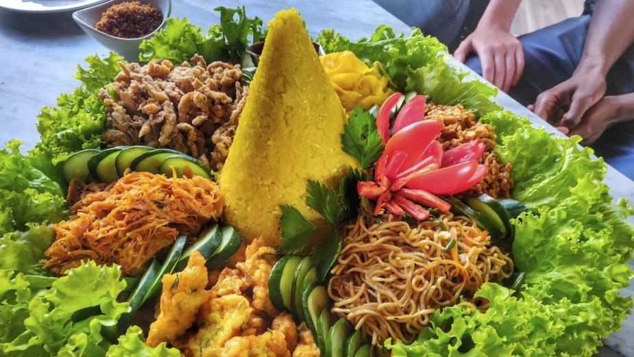 Tradycyjne indonezyjskie jedzenie – żółty ryż gotowany z mlekiem kokosowym i kurkumą (nasi kuning) z mnóstwem pysznych dodatków.