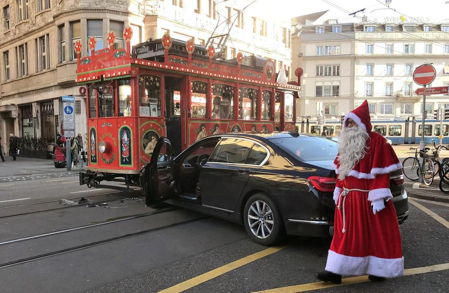 Driver of a Maerlitram (fairy tram), dressed as a Santa Claus, walks past a car which crashed into t