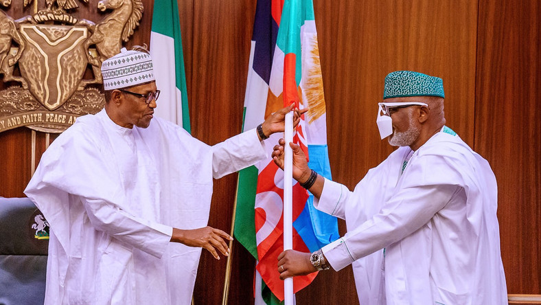 President Muhammadu Buhari presents All Progressives Congress (APC)'s flag to Ondo state Governor, Rotimi Akeredolu. [Twitter/@NigeriaGov]