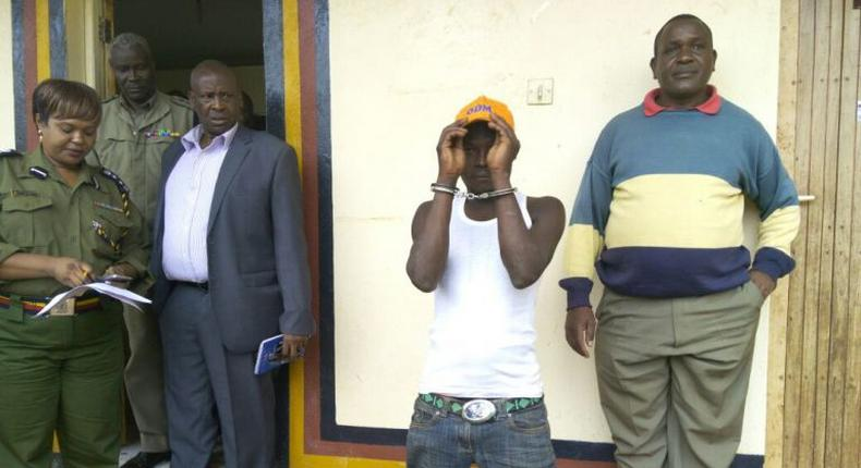 Julius Mwithalii (in handcuffs) after he was arrested for clinging on to Raila's chopper in Meru.
