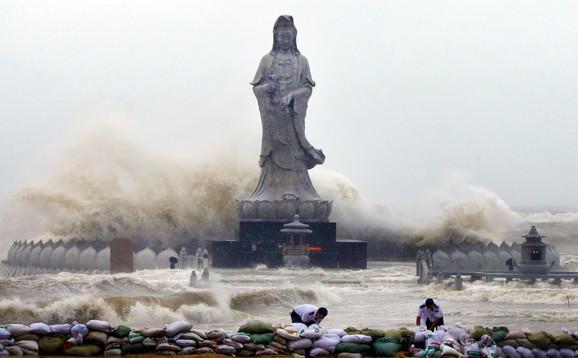 Ljudi postavljaju džakove za odbranu od nadolazeće vode nakon što je tajfun Dudžuan pogodio obalu u kineskom gradu Kvangdžou.