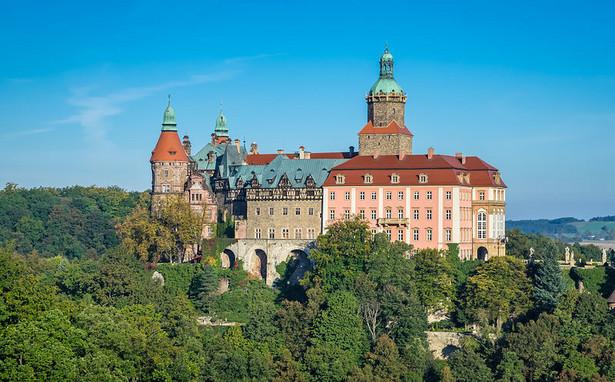 """Zamek Książ Usytuowany w Wałbrzychu zespół rezydencjalny jest częścią Książańskiego Parku Krajobrazowego. Znajduje się też na Szlaku Zamków Piastowskich. Jest to trzeci co do wielkości zamek w Polsce (po zamku w Malborku i Zamku Królewskim na Wawelu). Jego niewielka część, w tym znajdujący się w części centralnej zamek piastowski, jest udostępniona zwiedzającym. Okazały kompleks jest atrakcją w sumie trzech szlaków: Szlaku Ułanów Legii Nadwiślańskiej, Szlaku Zamków Piastowskich oraz czerwonego szlaku turystycznego biegnącego od cisu """"Bolko"""" przez zamek, Świebodzice i Witoszów Górny do Bystrzycy Górnej. Fot. Jar.ciurus / Wikimedia Commons, lic. cc-by-sa"""