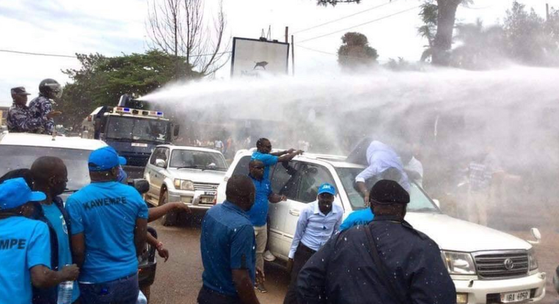 Besieged Uganda's opposition leader Dr Kizza Besigye, lies on top of his car after knocked down by police water canon. (Twitter)
