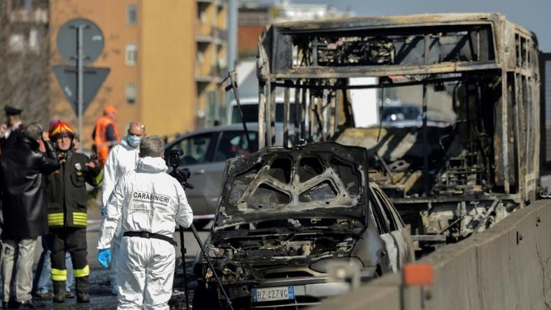 Forensic policemen and firefighters work near the wreckage of a school bus after rescuing some 50 children as the driver torched the vehicle, southeast of Milan.