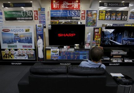 A man sitting on a sofa looks at a Sharp Corp's Aquos TV at an electronics retailer in Tokyo