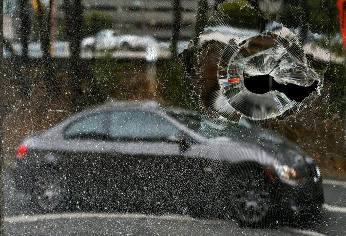A car is reflected in a damaged window to a building after protests against the police shooting of K