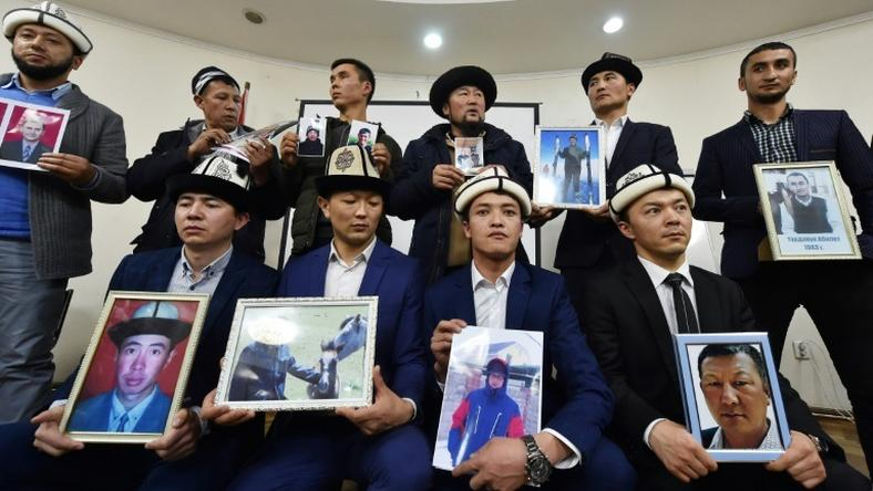 "Kyrgyz family members hold portraits of their relatives who they fear are being held in notorious ""re-education camps"" in China's Xinjiang region"