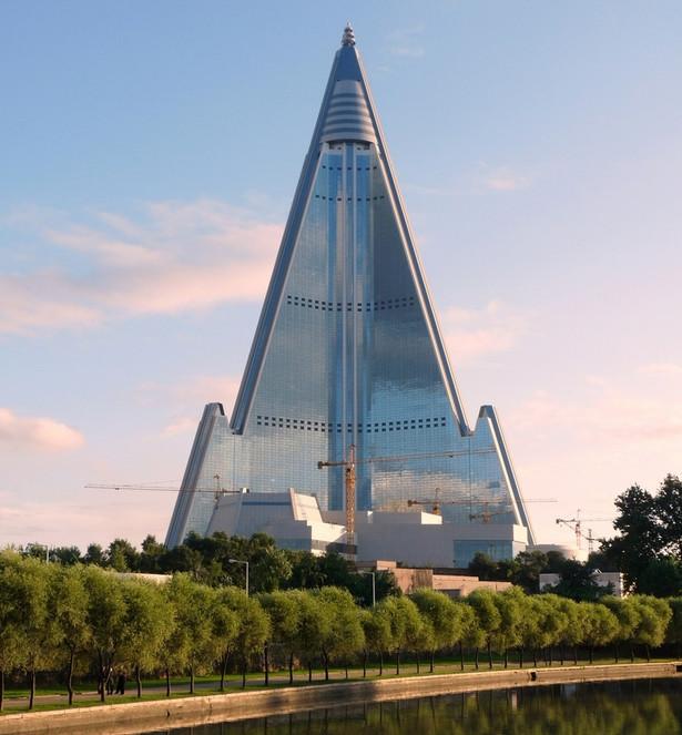 Budynek przedstawiony na zdjęciu to hotel Ryugyong. Liczący 330 metrów i 105 pięter gmach jest największym budynkiem w kraju. Jego budowa rozpoczęła się w 1987 roku, jednak w 1992 roku przerwano ją na szesnaście lat. W 2008 roku budowę wznowiono i władze twierdzą, że hotel zostanie ukończony w tym roku.